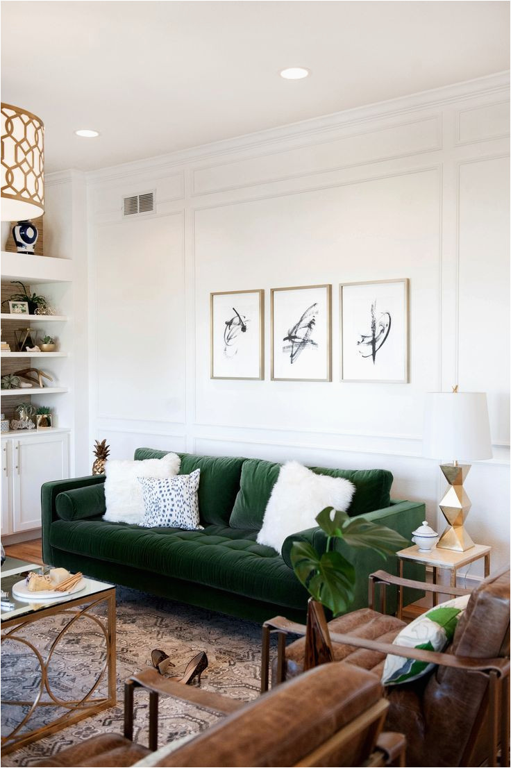 green velvet sofa with white fur pillows and brown leather