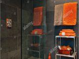 Orange Bathroom Rugs and towels Bright orange towels In Bathroom with Slate Tiles Stock